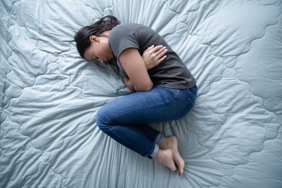 Teenager, der ligger krummet sammen på en seng